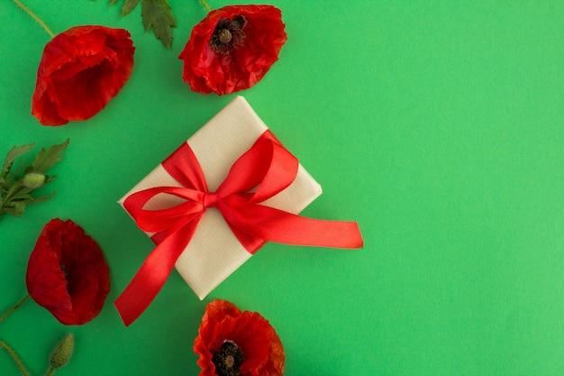 緑に赤いリボンと赤いポピーのギフトボックス