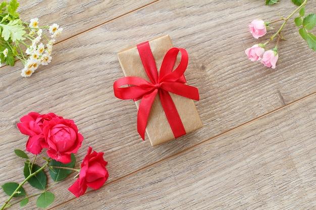 赤いリボン、美しいバラ、木製の背景にカモミールの花とギフトボックス。休日に贈り物をするという概念。上面図。