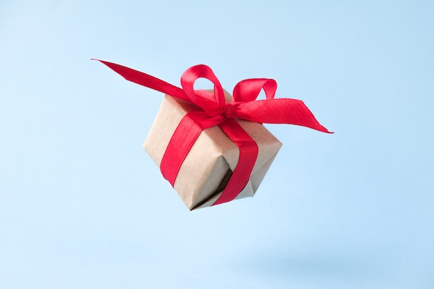Gift box with red ribbon on blue background.