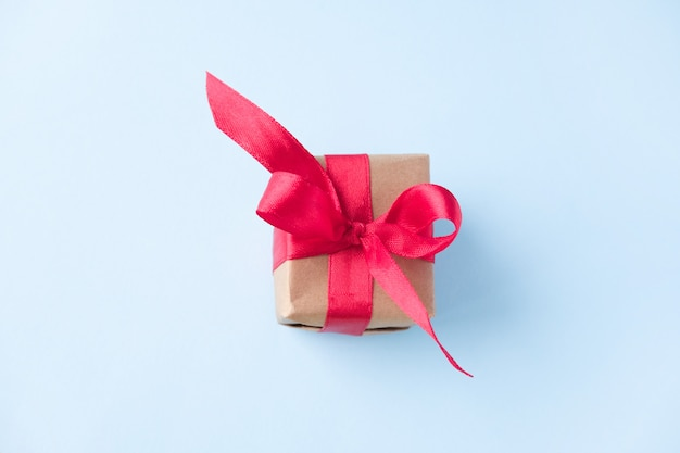 Gift box with red ribbon on blue