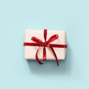 Gift box with red ribbon on blue,