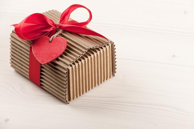 나무 테이블에 빨간 리본 활과 하트 모양의 태그가 있는 선물 상자