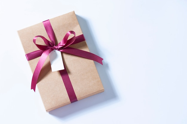 Gift box with red ribbon bow and blank label tag, top view