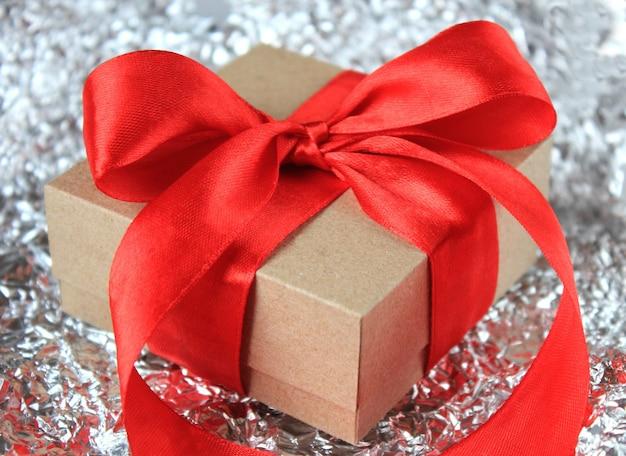 Подарочная коробка с бантом из красной ленты на блестящей поверхности