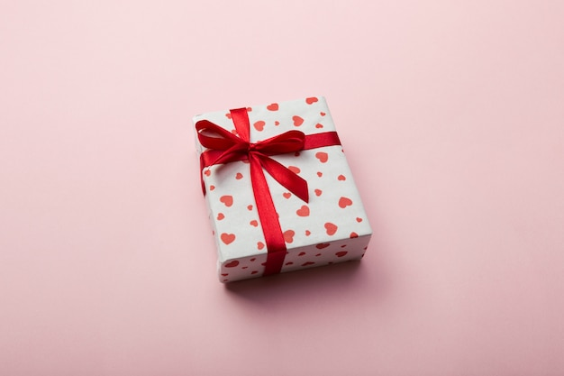 Gift box with red ribbon and heart on coral