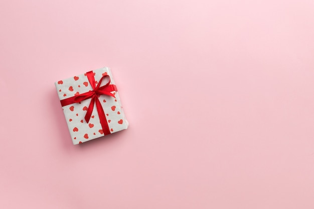 Gift box with red ribbon and heart on pink