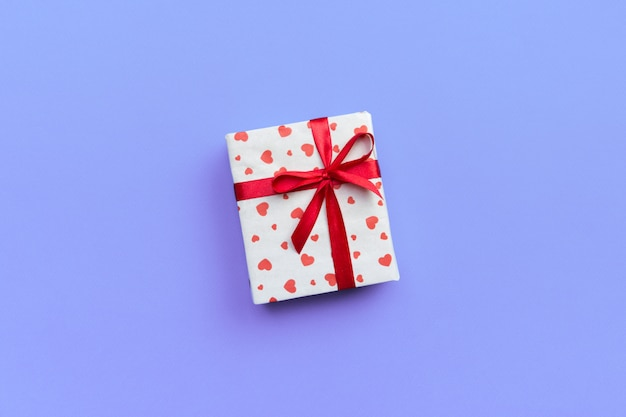Gift box with red ribbon and heart on purple background