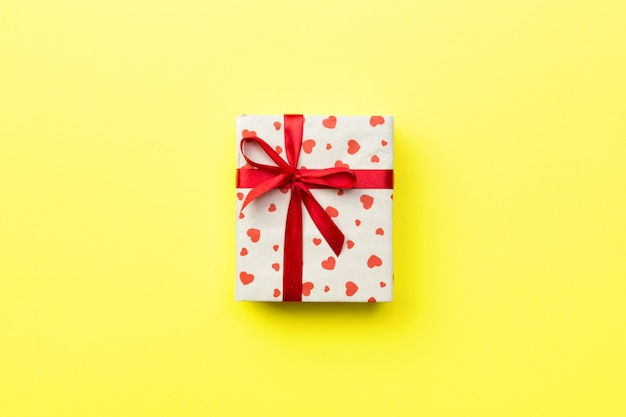 Gift box with red ribbon and heart on yellow background, top view with copy space for text