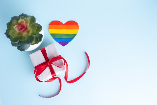 Gift box with a red ribbon, a home flower in a pot and a paper rainbow heart on a gentle blue background. lgbt congratulations concept