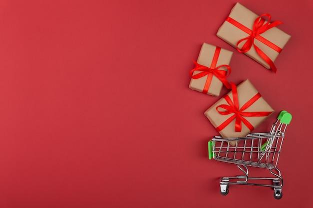 Подарочная коробка с красной лентой в мини-тележке для продуктов на красном фоне