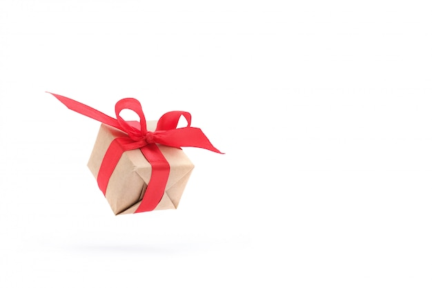 Gift box with red ribbon isolated in air on white.