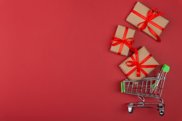 Gift box with red ribbon in mini grocery cart on red background