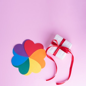 Gift box with red ribbon and multicolored flower shape with rainbow petals on a pink surface, copy space, square frame. lgbt concept