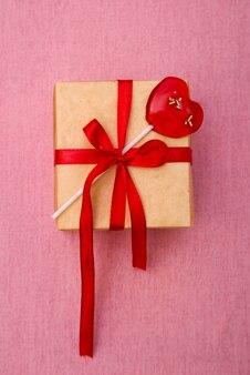 Подарочная коробка с красной лентой на розовом фоне
