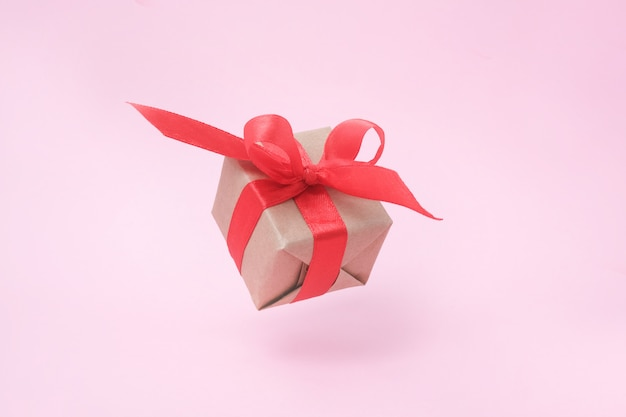 Gift box with red ribbon on pink.