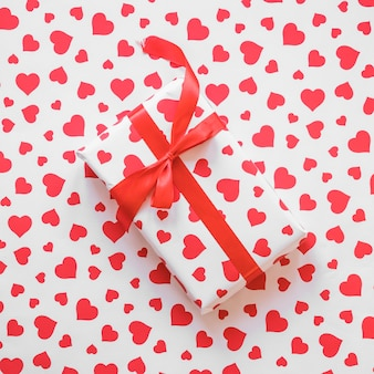 Gift box with red ribbon on table