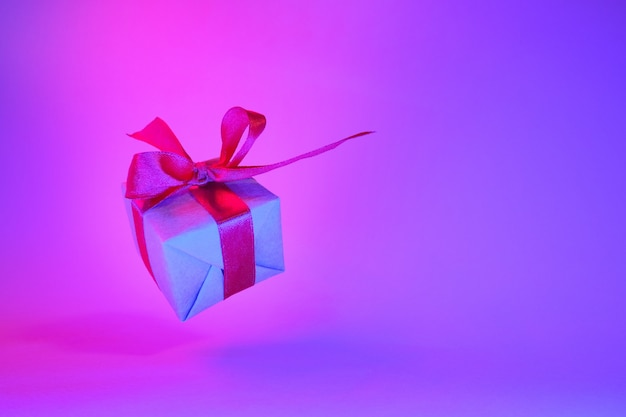 Gift box with red ribbon on trendy neon blue