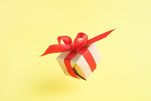 Gift box with red ribbon on yellow