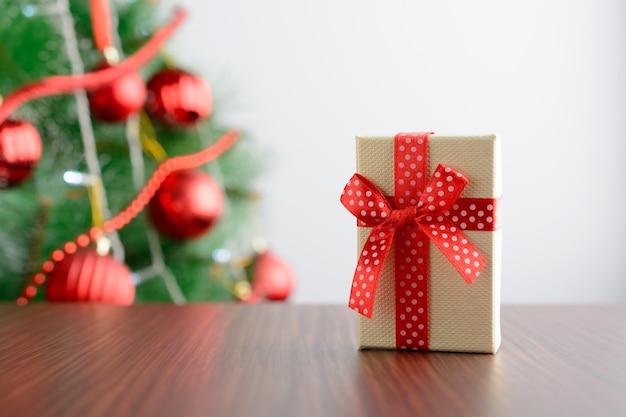 흰색 바탕에 전나무 나무에서 테이블에 빨간 ribbonâ 선물 상자.