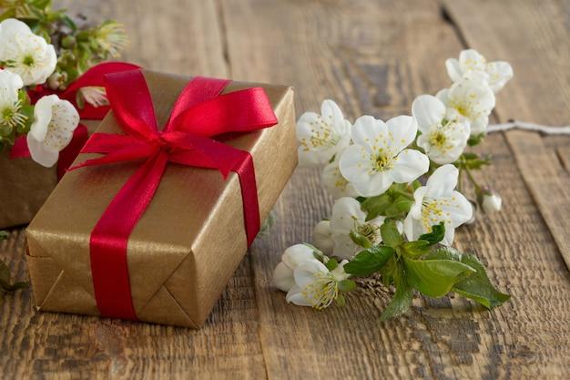 赤いリボン、古い木の板に美しいジャスミンの花の枝が付いたギフトボックス。休日に贈り物をするという概念。