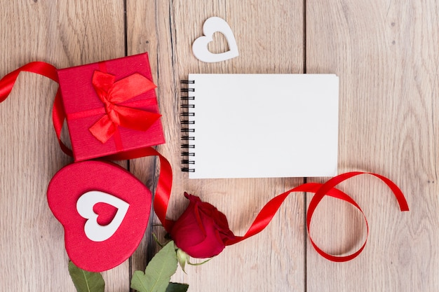 Gift box with red rose and notepad on table