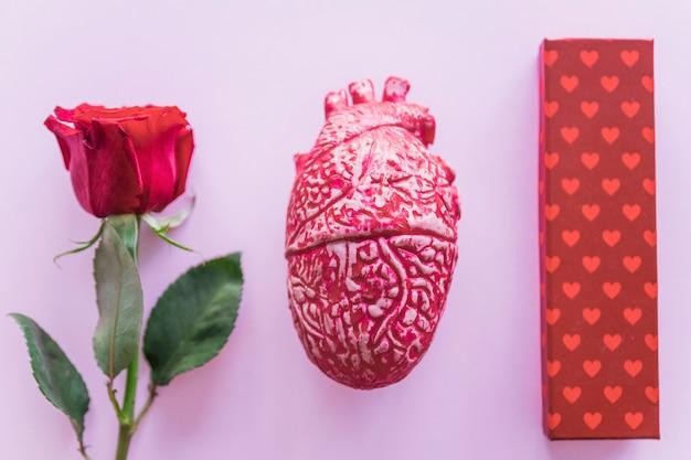 Confezione regalo con rosa rossa sul tavolo