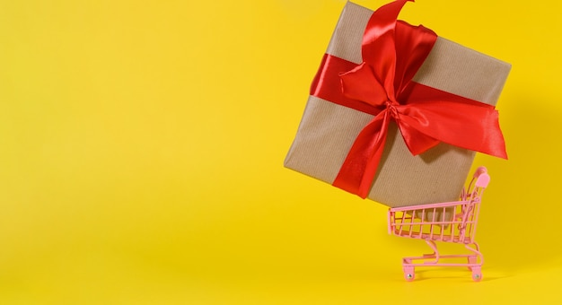 Gift box with a red silk bow in a miniature metal trolley on a yellow surface. party backdrop, surprise, seasonal sale