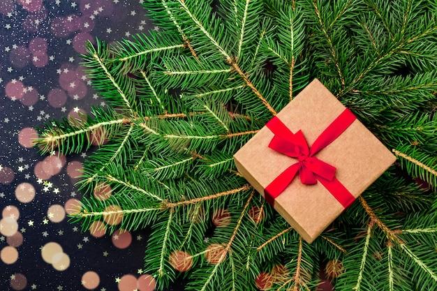 ボケ効果のあるクリスマスツリーの枝に赤いテープが付いたギフトボックス