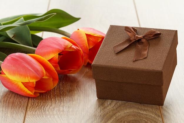 나무 판자에 빨간 튤립이 있는 선물 상자. 인사말 카드 개념입니다.