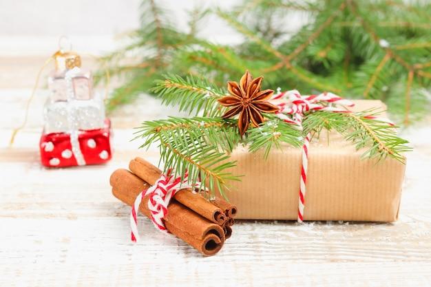 Подарочная коробка с красно-белой лентой из шпагата, обернутая бумагой с анисом и корицей