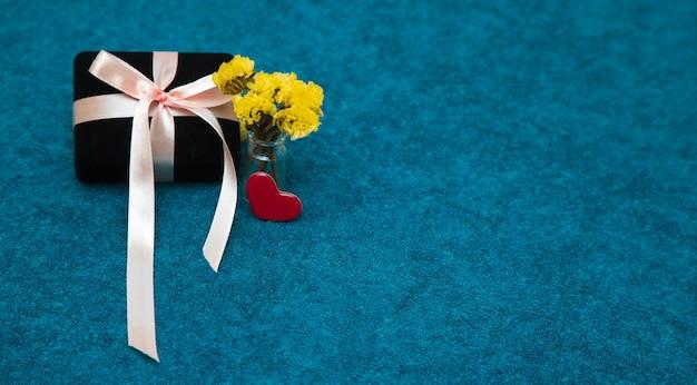 リボンとハートと黄色い花のギフトボックス。バレンタインデーのためのcoposy