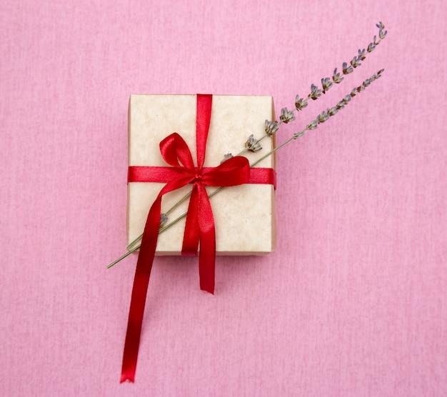 Подарочная коробка с лентой и соцветиями лаванды на розовом фоне