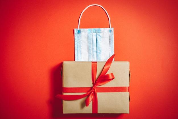 Подарочная коробка с лентой и медицинской защитной маской на красном фоне. скопируйте пространство.