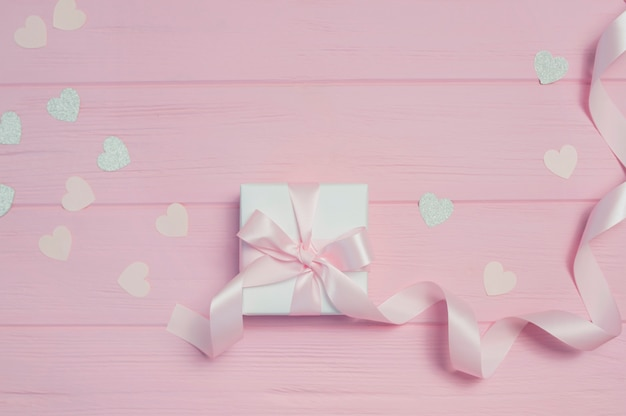 Gift box with ribbon and confetti in shape of heart