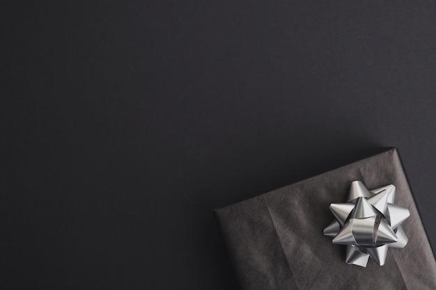 Подарочная коробка с серебряным бантом на темном столе. черная пятница, рождество или день рождения