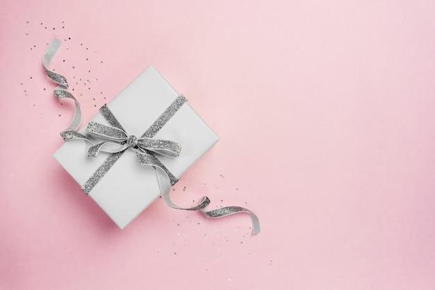 Подарочная коробка с бантом из серебряной ленты на розовом с блестками