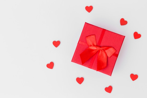 Gift box with small hearts on white table