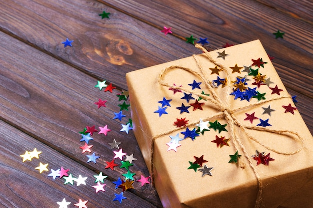 Gift box with star. creative concept with festive decor. confetti stars, red, yellow with gift box. explosion of confetti