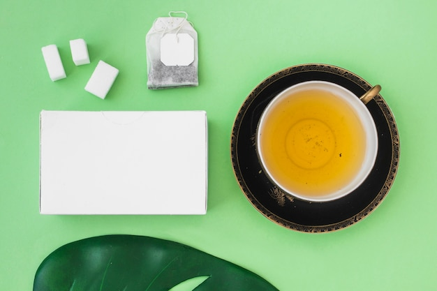 Gift box with sugar cube, tea bag, leaf and herbal tea cup on green background