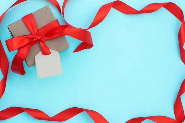 タグと青色の背景に赤の弓のギフトボックス。上面図。フラット横たわっていた。幸せな父の日、休日、招待状、誕生日、バレンタインデーのコンセプトです。