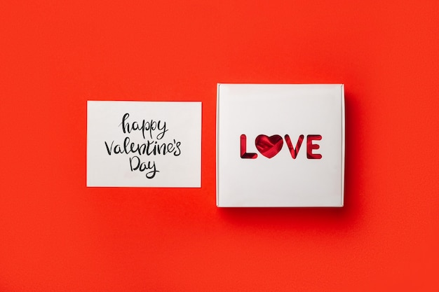 Gift box with text love and card on a red background. composition valentine's day. banner. flat lay, top view.