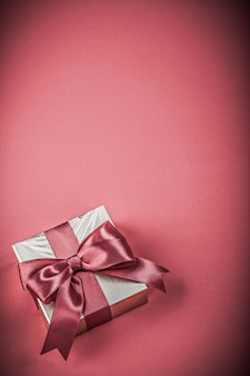 Gift box with tied ribbon on red background holidays concept