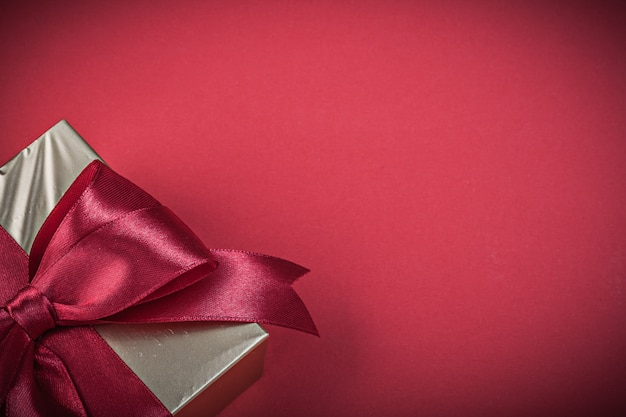 Gift box with tied tape on red background holidays concept