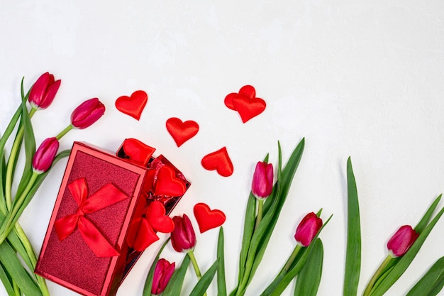 Gift box with valentines and red tulips on a textured white background with copy space