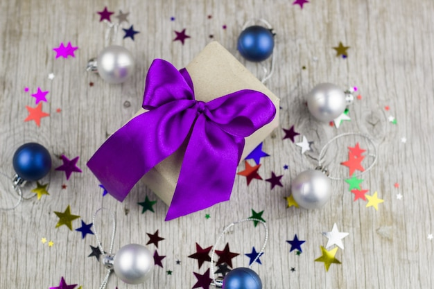 Gift box with violet satin ribbon on the wooden table