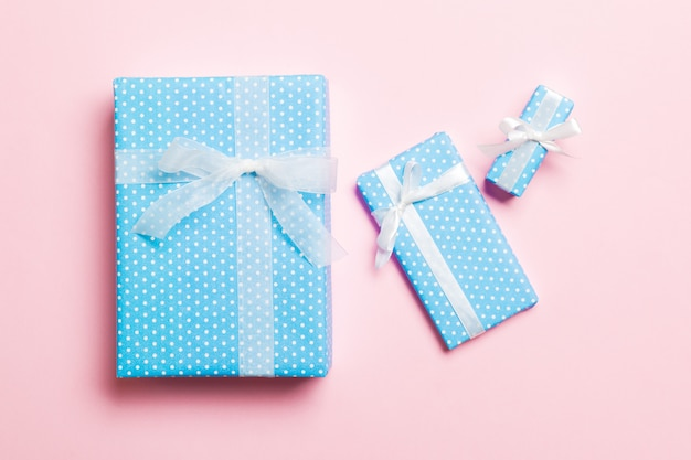 Gift box with white bow for christmas or new year day on pink background, top view