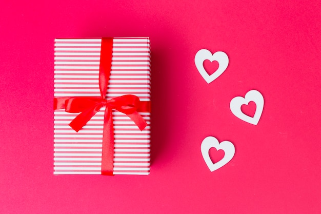 Gift box with white hearts on table