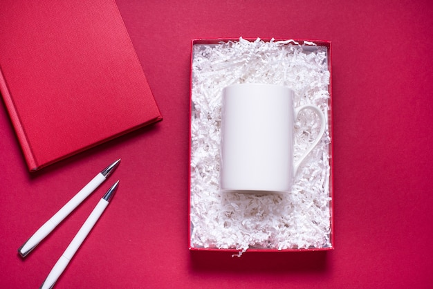 Gift box with white paper filler and coffee mug, flat lay on red background
