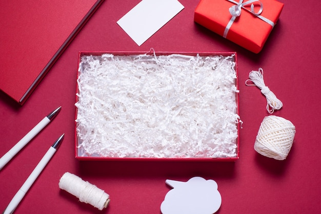 Gift box with white paper filler, flat lay on red background