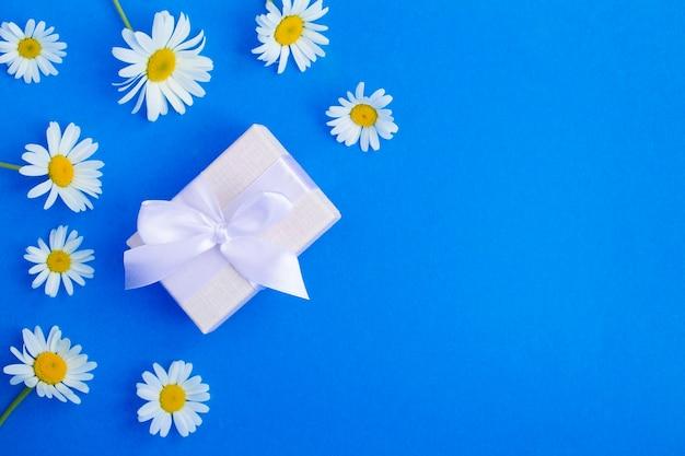 흰색 리본 및 카모마일 파란색 테이블에 선물 상자. 상위 뷰. 공간을 복사합니다.